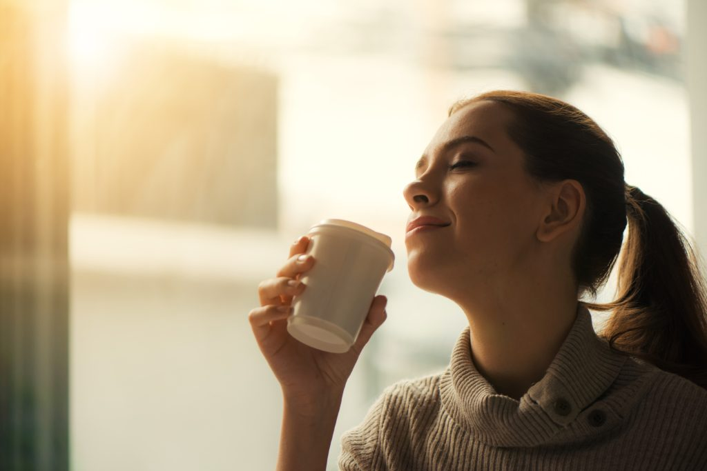 Lady smiling while smelling coffee